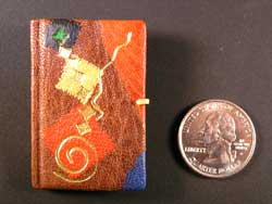 miniature book next to a U.S. quarter